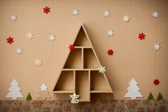 L'albero di Natale ha modellato il contenitore e le decorazioni di regalo, sul fondo del cartone Fotografia Stock