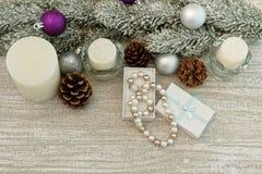 L'albero di Natale si ramifica, candele e collana della perla in un contenitore di regalo Fotografie Stock