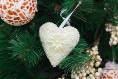L'albero di Natale si ramifica con la palla arancio e i ornamen bianchi del cuore Fotografia Stock