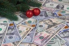 L'albero di Natale si ramifica palle rosse sul fondo dei soldi Fotografia Stock