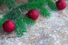 L'albero di Natale si ramifica, palle rosse sulle sedere di legno isolate dalla neve dell'inverno Immagine Stock