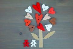 L'albero e due di amore del bottone riguarda il fondo di legno grigio Immagine Stock
