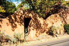 L'albero getta le ombre sulla parete dell'adobe su Canyon Road in Santa Fe, nuova fotografia stock libera da diritti