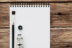 L'album in bianco con il piano degli strumenti di disegno pone il modello Immagini Stock
