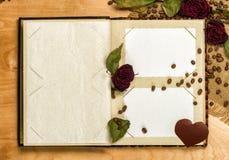L'album photos et sèchent les roses rouges sur la graine de café Image stock