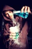 L'alchimista in laboratorio chimico prepara i liquidi magici fotografia stock libera da diritti