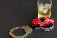 L'alcool, le manette e l'automobile giocano sul fondo di colore fotografia stock libera da diritti