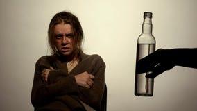 L'alcool s'est adonné à la femme regardant la bouteille de vodka, subissant la réadaptation image libre de droits