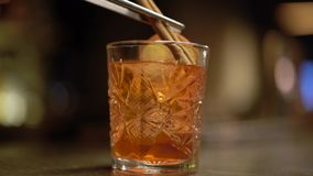 L'alcool sparato con l'arancia ed il ghiaccio è alla fine della tavola su Il barista mette la cannella nel vetro video d archivio