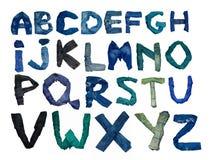 L'alfabeto inglese isolato è presentato dalle lettere che consistono dei vestiti dei jeans Immagine Stock