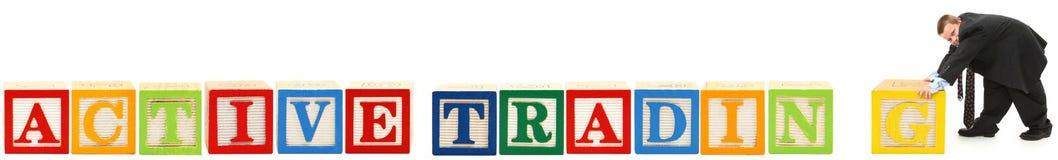L'alfabeto ostruisce il commercio attivo con il ragazzo in vestito Fotografie Stock