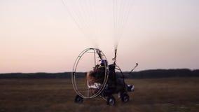 L'aliante del motore decolla con una ragazza e un uomo all'aeroporto che accelera e che decolla nel cielo dal paracadute archivi video