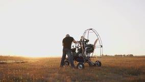 L'aliante del motore sta nel campo al tramonto con un'elica di legno, due piloti conduce un'esecuzione dei test del motore stock footage