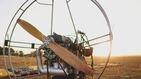 L'aliante del motore sta nel campo al tramonto con un'elica di legno ed il pilota presenta il paracadute e stock footage