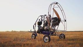L'aliante del motore sta nel campo al tramonto con un'elica di legno ed il pilota presenta il paracadute e video d archivio