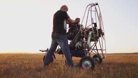 L'aliante del motore sta nel campo al tramonto con un'elica di legno, un riscaldamento di due piloti il motore prima del volo archivi video