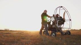 L'aliante del motore sta in un campo al tramonto con un'elica di legno, due piloti conduce un'esecuzione dei test del motore stock footage