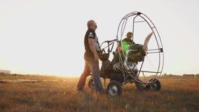 L'aliante del motore sta in un campo al tramonto con un'elica di legno, un riscaldamento di due piloti il motore prima del volo a archivi video