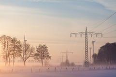 L'alimentation d'énergie raye des poteaux et le genertor de vent dans le brouillard Photographie stock