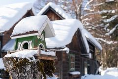 L'alimentatore dell'uccello di legno casalingo nell'inverno, sotto neve fotografia stock