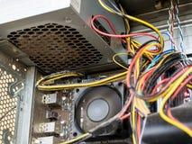 L'alimentazione elettrica ed i cavi dentro del caso con computer personale sono coperti di polvere molta polvere sotto il disposi fotografie stock