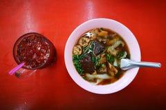 L'alimento asiatico ha bollito il quadrato cinese della pasta con tè nero tailandese sulla tavola rossa Fotografia Stock