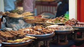L'alimento asiatico tradizionale è venduto al mercato di notte in Tailandia I pezzi del pollo fritto, le salsiccie, bacon sono a video d archivio