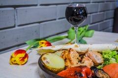 L'alimento caucasico con carne e vetro di vino rosso Piatto georgiano nazionale Un kebab con le verdure Tulipani immagine stock