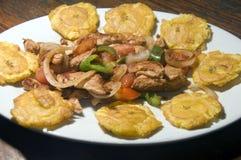 L'alimento cotto della fajita del pollo con i tostones locali ha fritto i plantani Immagine Stock