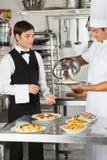L'alimento di Giving Customer del cuoco unico al cameriere Immagini Stock