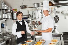 L'alimento di Taking Customer del cameriere dal cuoco unico fotografia stock libera da diritti