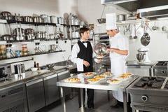 L'alimento di Taking Customer del cameriere dal cuoco unico Fotografie Stock Libere da Diritti