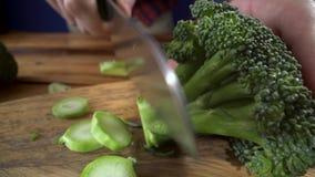 L'alimento sano, cuoco taglia un mazzo di broccoli Assortimento sano delle verdure e della frutta con i legumi video d archivio