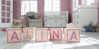 L'alina de nom écrit avec les cubes en bois en jouet chez la pièce du ` s des enfants Photographie stock libre de droits
