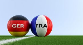L'Allemagne contre Match de football de Frances - ballons de football en couleurs nationales d'allemand et de Frances sur un terr Photographie stock libre de droits