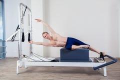 L'allenamento del riformatore di Pilates esercita l'uomo alla palestra Fotografia Stock