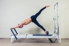 L'allenamento del riformatore di Pilates esercita l'uomo alla palestra Fotografie Stock