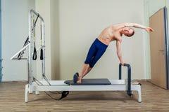L'allenamento del riformatore di Pilates esercita l'uomo alla palestra dell'interno Fotografia Stock