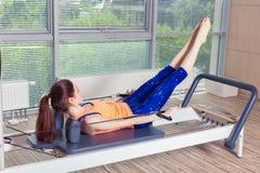 L'allenamento del riformatore di Pilates esercita la donna alla palestra dell'interno Fotografia Stock