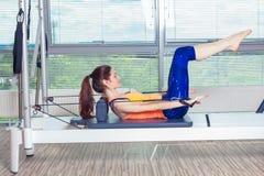 L'allenamento del riformatore di Pilates esercita la donna alla palestra dell'interno Immagini Stock Libere da Diritti