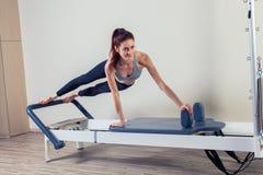 L'allenamento del riformatore di Pilates esercita la donna castana Immagine Stock