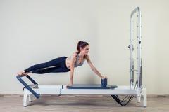 L'allenamento del riformatore di Pilates esercita la donna castana Fotografia Stock