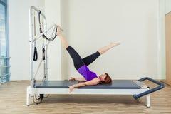 L'allenamento del riformatore di Pilates esercita la donna castana alla palestra dell'interno Immagine Stock