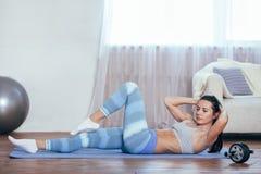 L'allenamento della donna a casa, lei si siede su Fotografia Stock