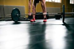 L'allenamento della donna con il bilanciere alla palestra, prepara alzare i pesi Immagini Stock