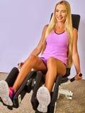L'allenamento della ragazza sulla gamba introduce la palestra di sport Immagine Stock