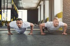 L'allenamento di forma fisica di due uomini, spinge aumenta o plancia Immagini Stock