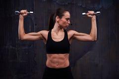 L'allenamento di forza della femmina sicura muscolare che fa il bicipite arriccia Fotografie Stock Libere da Diritti