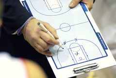 L'allenatore di pallacanestro scrive le tattiche sulla preparazione del bordo Fotografia Stock