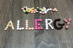 L'allergia di parola scritta le pillole del whith su un fondo di legno Immagine Stock Libera da Diritti